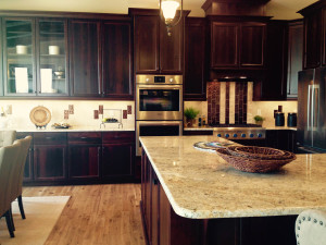 Gorgeous cherry wood kitchen cabinets with cream and maroon tile backsplash.